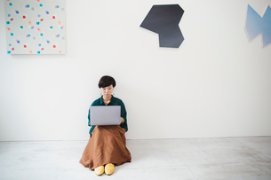 Woman with short black hair wearing green shirt sitting on floor in art gallery, balancing laptop onの写真素材 [FYI02260711]