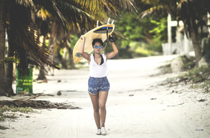 Young woman walking along a beach carrying a surfboard.の写真素材 [FYI02260715]
