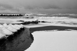 Snow-covered wave breakers near an inlet in winter.の写真素材 [FYI02260720]