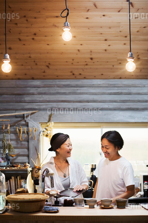 Man and woman standing in a kitchen, cleaning dishes, smiling at each other.の写真素材 [FYI02260723]