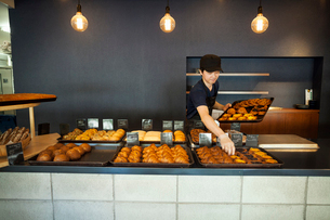 Man working in a bakery, placing freshly baked croissants and cakes on large trays on a counter.の写真素材 [FYI02260724]