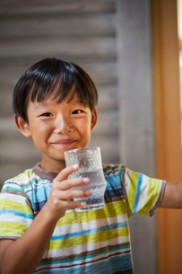 Portrait of boy with black hair wearing stripy T-shirt, holding drinking glass, smiling at camera.の写真素材 [FYI02260730]