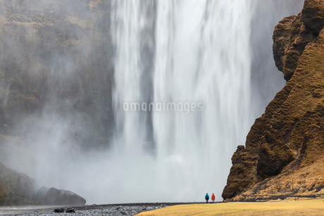 Landscape with rear view of person standing next to a tall waterfall.の写真素材 [FYI02260731]