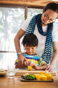 Man and boy standing at a table, preparing corn on the cob, smiling.の写真素材 [FYI02260735]