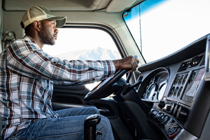 Black man truck driver in the cab of his commercial truck.の写真素材 [FYI02260769]