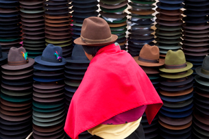 Rear view of woman wearing brown hat and bright pink poncho selling traditional Ecuadorian felt hatsの写真素材 [FYI02260777]
