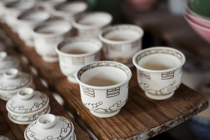 High angle close up of white cups and lids in a Japanese porcelain workshop.の写真素材 [FYI02260788]