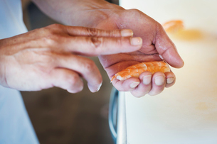 Close up of chef holding a piece of crab, making sushi.の写真素材 [FYI02260790]