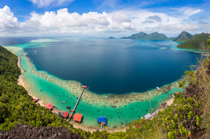 Wide angle view along coastline of tropical island, mountains in the distance.の写真素材 [FYI02260792]