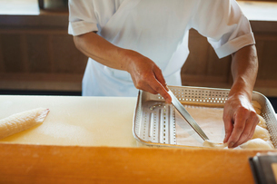 High angle close up of chef working at a counter at a Japanese sushi restaurant, placing slices of fの写真素材 [FYI02260794]