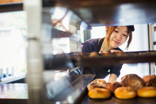 Woman working in a bakery, placing large trays with freshly baked rolls on a trolley.の写真素材 [FYI02260798]