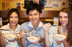 Three smiling people sitting sidy by side at a table in a restaurant, eating from bowls using chopstの写真素材 [FYI02260817]