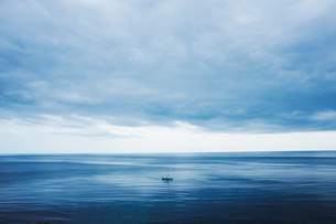 View across a calm sea to the horizon and a cloudy sky. A small yacht, day boat under motor power.の写真素材 [FYI02260836]