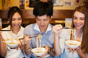 Three smiling people sitting sidy by side at a table in a restaurant, eating from bowls using chopstの写真素材 [FYI02260841]