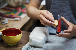 Close up of woman working in a Japanese porcelain workshop, holding red paint stick and sponge.の写真素材 [FYI02260853]