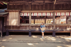 Young woman wearing blue dress and holding hat standing at Shinto Sakurai Shrine, Fukuoka, Japan.の写真素材 [FYI02260858]
