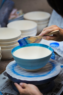 Close up of person working in a Japanese porcelain workshop, painting white bowls with blue glaze.の写真素材 [FYI02260873]
