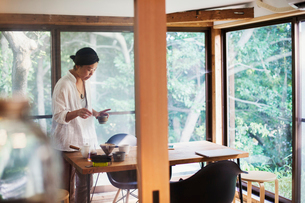 Woman standing indoors by a table, holding small bowl.の写真素材 [FYI02260876]