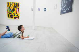 Boy with short black hair lying on floor in art gallery with pen and paper, looking at modern paintiの写真素材 [FYI02260882]