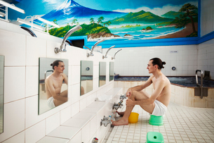 A young Western man seated in a towel, at the shower area, showering before he enters the public batの写真素材 [FYI02260884]