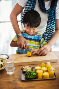 Man and boy standing at a table, preparing corn on the cob, smiling.の写真素材 [FYI02260894]