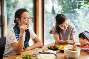 Man, woman and young girl sitting round a table with bowls of food, eating together.の写真素材 [FYI02260896]
