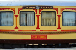 Train carriages in red and yellow livery colours, at a station in Rajasthan. The Palace on Wheels.の写真素材 [FYI02260916]