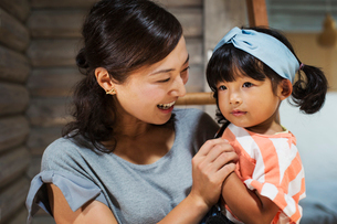 Smiling woman holding young girl with black pigtails wearing blue hairband.の写真素材 [FYI02260923]