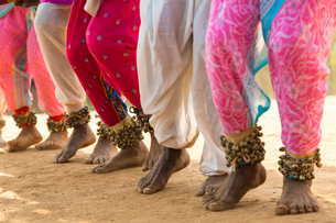 Low section view of barefoot dancers in a row on a street, wearing pink trousers and ankle bells.の写真素材 [FYI02260930]