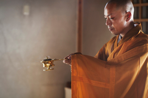 Side view of Buddhist monk with shaved head wearing golden robe kneeling indoors in a temple, holdinの写真素材 [FYI02260938]