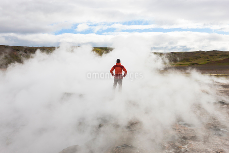 Rear view of woman standing by geothermal pools, surrounded by steam.の写真素材 [FYI02260947]