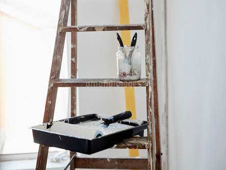 A wooden paint splashed ladder, a jar with two paintbrushes and a paint tray and roller.の写真素材 [FYI02260950]