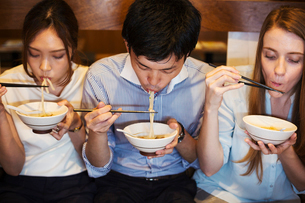 High angle view of three people sitting sidy by side at a table in a restaurant, eating from bowls uの写真素材 [FYI02260953]