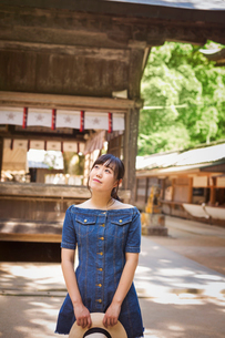 Young woman wearing blue dress and holding hat at Shinto Sakurai Shrine, Fukuoka, Japan.の写真素材 [FYI02260964]