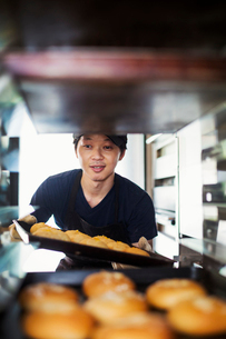 Man working in a bakery, placing large trays with freshly baked rolls on a trolley.の写真素材 [FYI02260968]