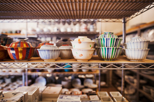 Close up of selection of ceramic bowls with lids on a shelf in a Japanese porcelain workshop.の写真素材 [FYI02260972]