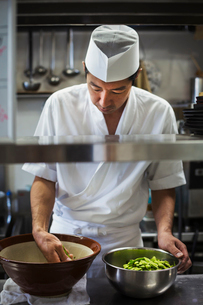 Chef working in the kitchen of a Japanese sushi restaurant, preparing bowl of edamame beans.の写真素材 [FYI02260986]