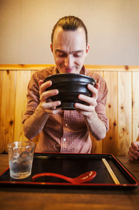 A western man in a noodle restaurant, with a noodle bowl lifting it with two hands to drink from it.の写真素材 [FYI02260993]