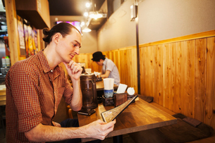 A western man in a noodle restaurant, reading from the menu.の写真素材 [FYI02260995]