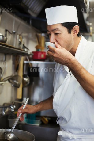Chef working in the kitchen of a Japanese sushi restaurant, tasting food.の写真素材 [FYI02261003]