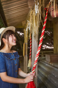 Young woman wearing blue dress and hat pulling on red rope at Shinto Sakurai Shrine, Fukuoka, Japan.の写真素材 [FYI02261008]