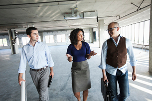Mixed race team of business people touring a new empty raw office space.の写真素材 [FYI02261009]
