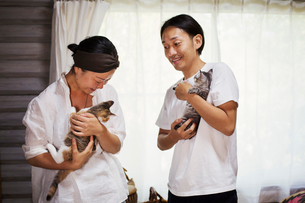 man and woman standing indoors, each holding calico cat with white, black and brown fur.の写真素材 [FYI02261017]