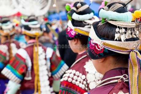 Rear view of girls wearing colourful traditional Chinese costumes and headdresses dancing at a festiの写真素材 [FYI02261020]