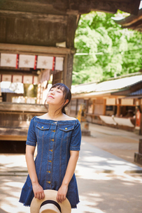 Young woman wearing blue dress and holding hat at Shinto Sakurai Shrine, Fukuoka, Japan.の写真素材 [FYI02261026]