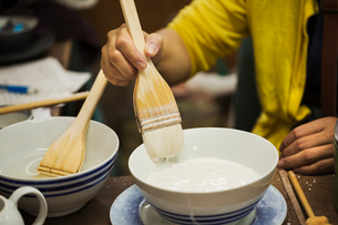 Close up of person working in a Japanese porcelain workshop, glazing white bowls with paintbrush.の写真素材 [FYI02261027]