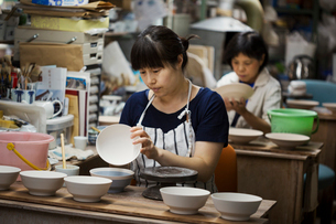 Two women sitting in a workshop, working on Japanese porcelain bowls.の写真素材 [FYI02261034]