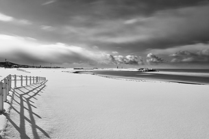 Fence running along a snow-covered beach near the ocean in winter.の写真素材 [FYI02261035]
