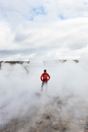 Rear view of woman standing by geothermal pools, surrounded by steam.の写真素材 [FYI02261037]