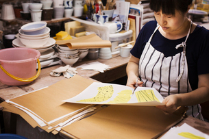 Woman sitting in a Japanese porcelain workshop, cutting out design patterns with a pair of scissors.の写真素材 [FYI02261043]